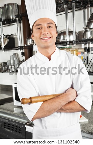 Portrait of happy chef standing with arms crossed in restaurant kitchen - stock photo