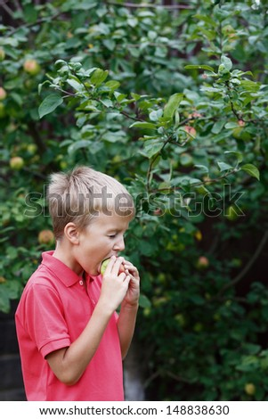 Portrait of happy child eating red apple outdoors in autumn
