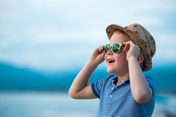 Portrait of happy child in sunglasses on the beach. Summer vacation concept. Smiling kid boy in hat and glasses near sea.