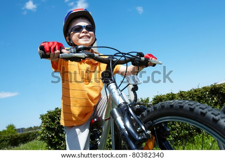 Portrait of happy child on bicycle against blue sky