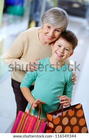 Portrait of happy child with paperbags and his grandmother in the mall