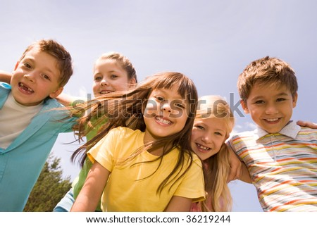 Portrait of happy children embracing each other and laughing with pretty girl in front - stock photo