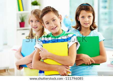 Portrait of happy classmates with books looking at camera in classroom