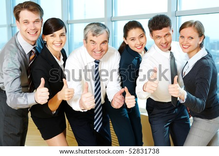 Portrait of happy co-workers looking at camera with smiles and showing sign of okay