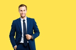 Portrait of happy confident businessman in blue suit and tie, isolated against yellow color background. Business success concept. Smiling man at studio picture. Copy space for some text or slogan.