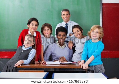Portrait of happy confident male and female teachers with schoolchildren together at desk in classroom