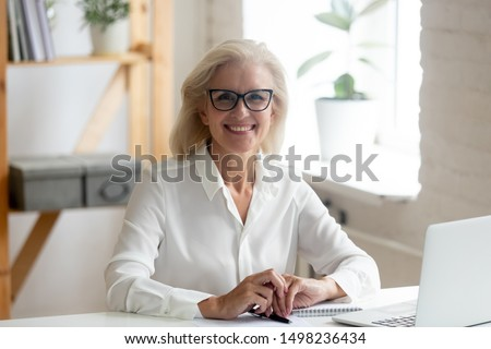 Portrait of happy confident senior grey-haired businesswoman in spectacles sit at office desk look at camera smiling, overjoyed glad aged woman worker wear glasses posing making picture at workplace
