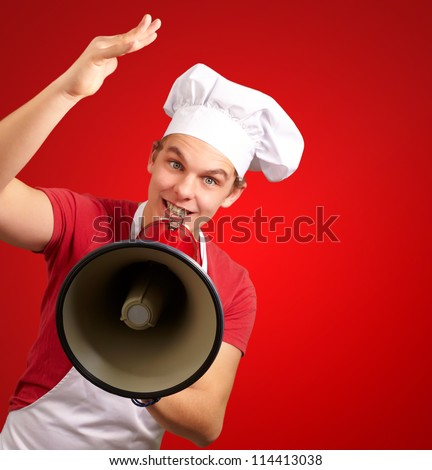 portrait of happy cook man shouting using megaphone over red background