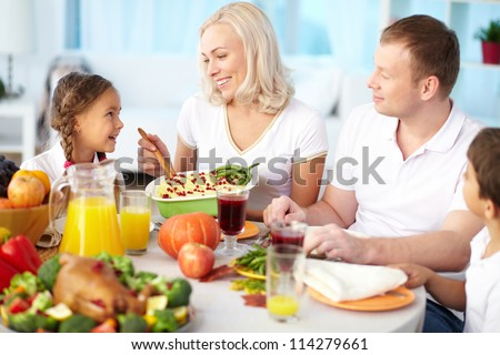 Portrait of happy couple and their children sitting at festive table and going to eat mashed potatoes