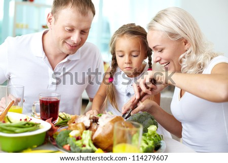 Portrait of happy couple and their daughter sitting at festive table and going to eat roasted turkey - stock photo