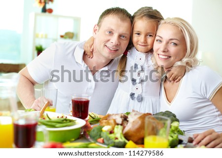 Portrait of happy couple and their daughter sitting at festive table and looking at camera