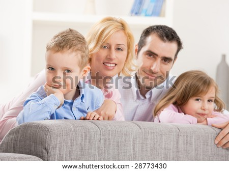 Portrait of happy couple and their two children, smiling. Selective focus on boy.