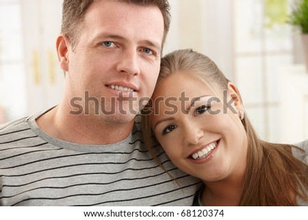 Portrait of happy couple at home, smiling woman leaning on man's shoulder.