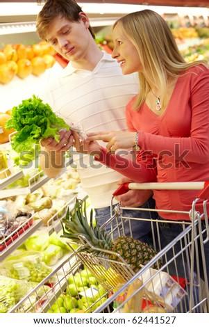 Portrait of happy couple choosing greenery in supermarket