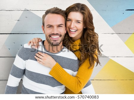 Portrait of happy couple embracing each other against wooden background