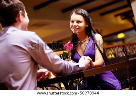Portrait of happy couple holding by hands and looking at each other