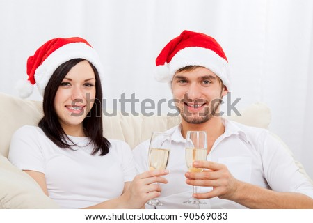 Portrait of happy couple in christmas hats with glass of champagne looking at camera and smiling, sitting indoors at home