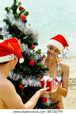 Portrait of happy couple in Santa caps near xmas firtree on the beach