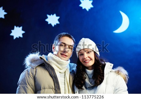 Portrait of happy couple looking at camera with moon and stars above their heads