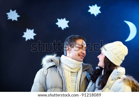 Portrait of happy couple looking at one another with moon and stars above their heads