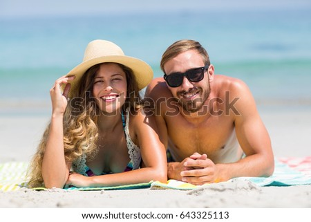 Portrait of happy couple lying on sand at beach during sunny day #643325113