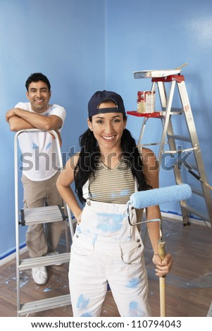 Portrait of happy couple painting blue color on wall
