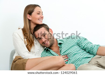 Portrait of happy couple relaxing on couch indoors.