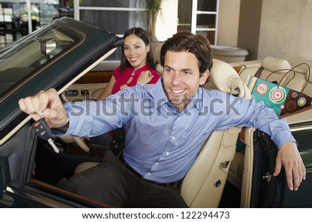 Portrait of happy couple sitting in convertible car with man showing keys