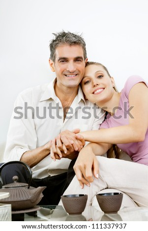 Portrait of happy couple sitting together while holding hands