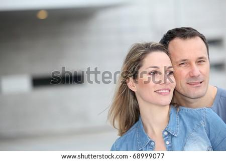 Portrait of happy couple standing outdoors - stock photo
