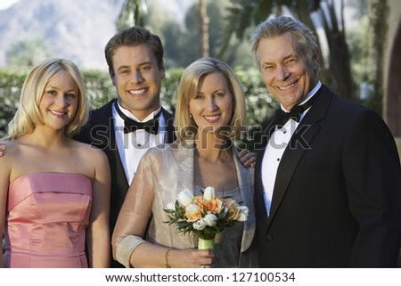 Portrait of happy couple standing with their family