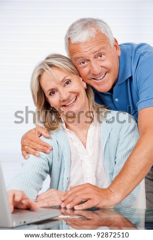 Portrait of happy couple using laptop together at home