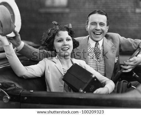 Portrait of happy couple waving in car