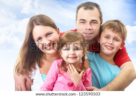 Portrait of happy couple with two children of blue sky background