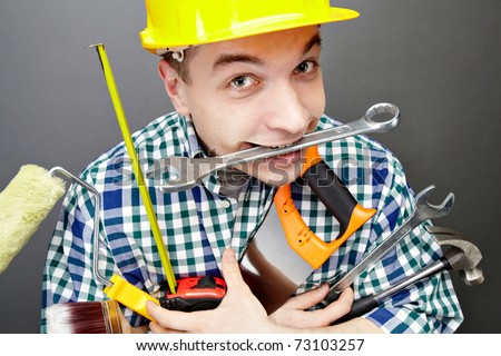 Portrait of happy craftsman with different tools in hands and wrench in mouth