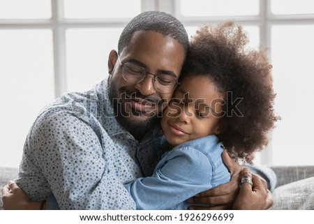 Portrait of happy cute Black girl hugging her beloved daddy and smiling with closed eyes. Peaceful affectionate dad and daughter kid enjoying time together, embracing, relaxing at home. Close up