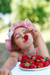 Portrait of Happy cute preteen girl  is eating strawberries at summer day. Soft focused