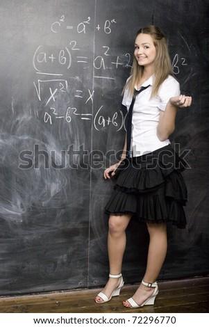 portrait of happy cute student with books calculator green apple near blackboard