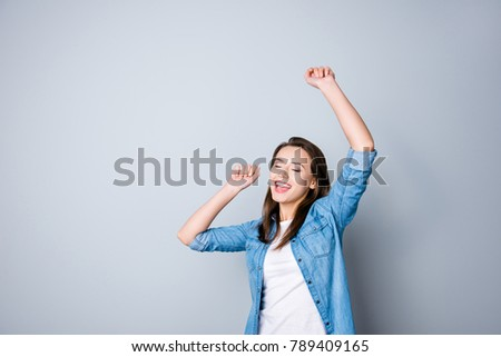 Portrait of happy cute young woman with toothy smile in casual oufit, raised hands, dancing because her dream comes true, standing over grey background