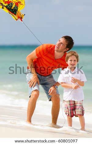 Portrait of happy dad and son flying kite together