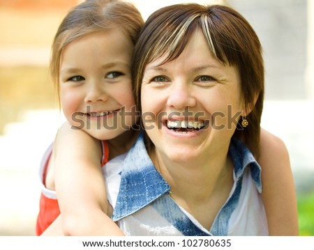Portrait of happy daughter enjoying a piggyback ride on mothers back outdoors
