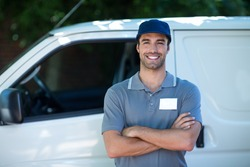 Portrait of happy delivery person with arms crossed while standing by van