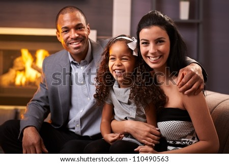 Portrait of happy diverse family at home, all smiling.