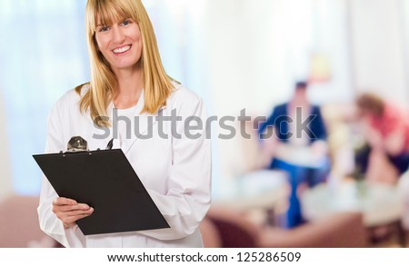 Portrait Of Happy Doctor Writing On Clipboard at the waiting room - stock photo