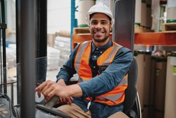 Portrait of happy driver wearing white helmet and vest sitting in forklift machine transporting goods in warehouse