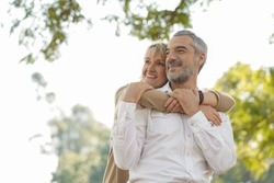 Portrait of happy elderly couple hug together, take care and love with good relationship, good health and romantic in the park, retirement insurance and lovely couple concept