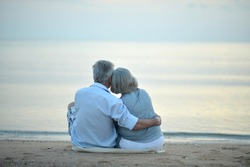 Portrait of happy elderly couple resting on tropical beach