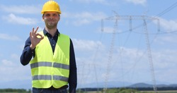 Portrait of Happy Engineer Man Looking Camera and Showing OK Sign with Electric Pillar Powerline Infrastructure