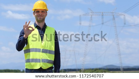 Portrait of Happy Engineer Man Looking Camera and Showing OK Sign with Electric Pillar Powerline Infrastructure #1172540707