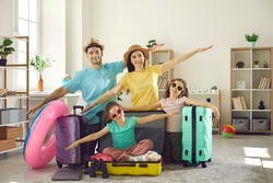 Portrait of happy family all set to leave on travel vacation. Smiling mom, dad and little kids ready for holiday trip spread arms in airplane wings gesture pretending to fly like a plane at home